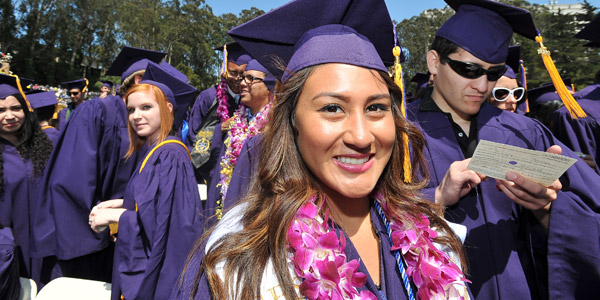 Female student at graduation in cap and gown smilings