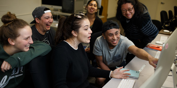 Group of students laughing as one points to the image on the computer